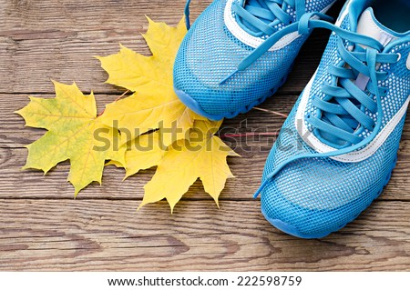 sports shoes and autumn leaves - stock photo