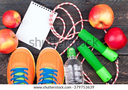 Sports shoes, jumping rope, apple, bottle of water and open blank notepad. Sport equipment. Healthy lifestyle, food, vegetarian and sport concept. Top view - stock photo