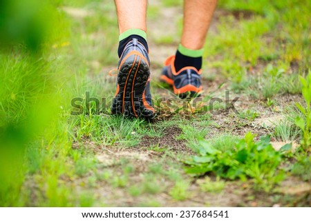 Sports shoes walking or jogging on green grass, man runner cross country running on trail in summer forest. Athlete male training and doing workout outdoors in nature. Jogging workout fitness concept. - stock photo
