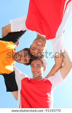 Sports team with heads together - stock photo