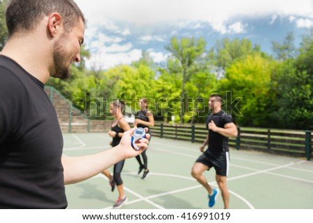 Sports trainer with stopwatch, cardio training outdoors - stock photo