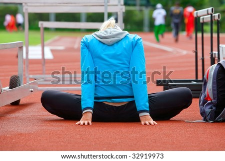 Sports warm-up of the young girl before race - stock photo