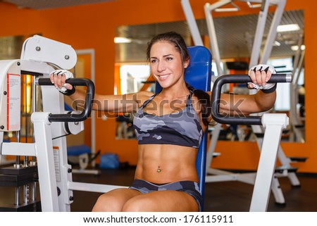 Sports woman doing exercises on power training apparatus in the gym.