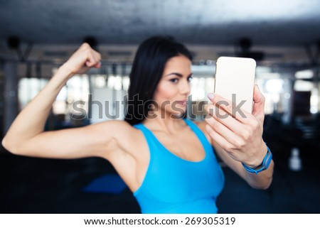 Sports woman making selfie on smartphone at gym. Focus on smartphone - stock photo