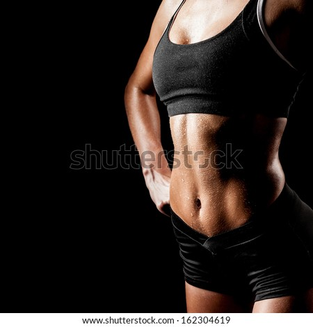 sports woman portrait wearing black sportswear over dark - stock photo