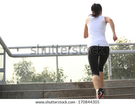 sports woman running at city pedestrian overpass stairs  - stock photo