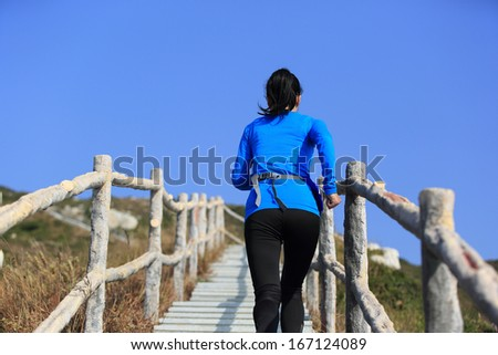 sports woman running climbing mountain stairs - stock photo