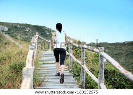 sports woman running on mountain stairs  - stock photo
