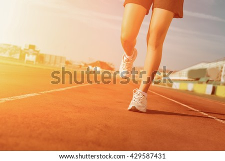 Sports woman running on tracks Female jogging on sunset. running shoes. Fitness health.  - stock photo