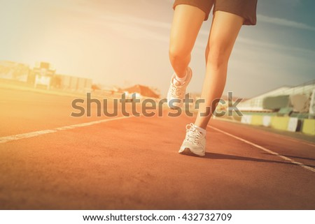 Sports woman running on tracks Female jogging. Woman jogging on sunset. Woman running on a running track. running shoes. Woman running and jogging concept. Girl running from Thailand. Fitness health.  - stock photo