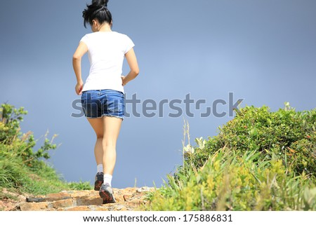 sports woman running up at mountain peak - stock photo