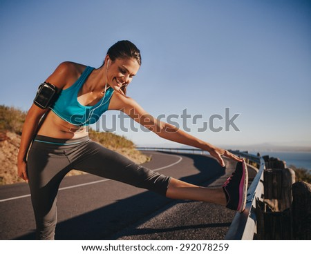 Sports woman stretching her leg on a guardrail before running outdoors. Female athlete getting ready for a run. - stock photo