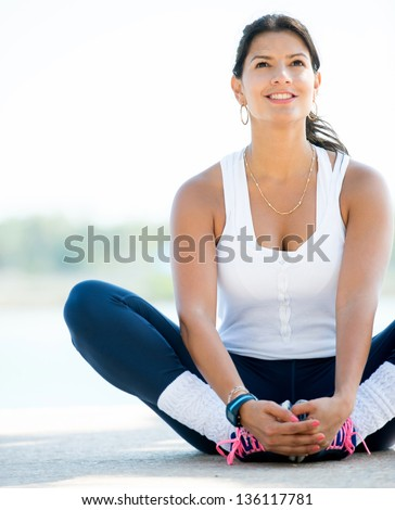 Sports woman stretching her legs outdoors before exercising - stock photo