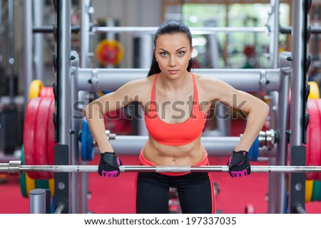 sports woman with weight barbell doing exercise in gym fitness center - stock photo
