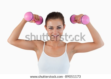 Sports woman working out with dumbbells against a white background