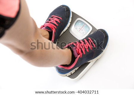 Sports women feet standing on weighing scale on white background. - stock photo