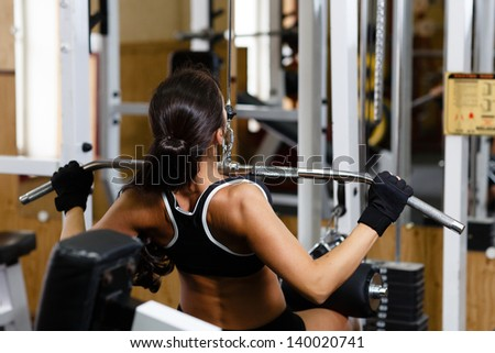 Sports young woman doing exercises in the gym on Lat Machine. - stock photo