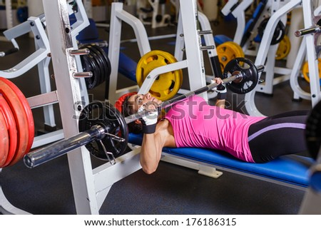 Sports young woman doing exercises with barbell on bench in the gym.  Bar Bench Press. - stock photo