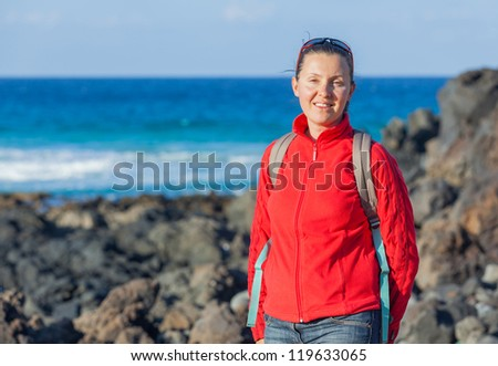Sports young woman with backpack. In the background of the sea - stock photo