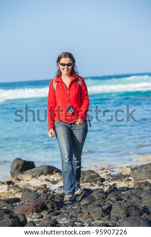 Sports young woman with backpack. In the background of the sea. Vertical view - stock photo