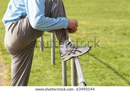 Sportsman attaching his registration tag to his running shoe before a race - stock photo