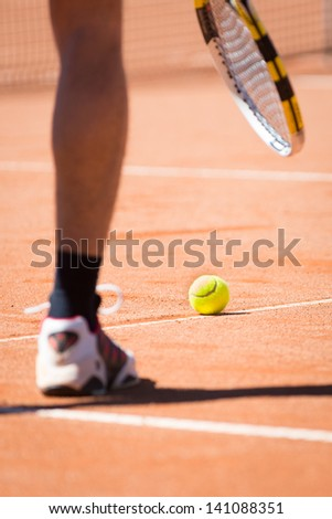 sportsman catchs up his tennis ball with racket