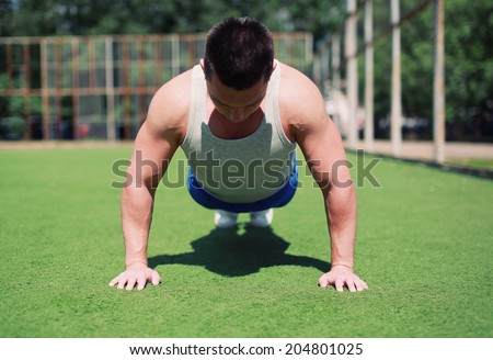Sportsman doing push-ups exercise outdoors, fitness, workout, sport - concept - stock photo