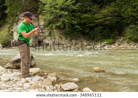 Sportsman fisherman shows catch trout in a mountain river. Interesting and hazardous confrontation between fishermen and fish. Healthy and emotional rest on a mountain river. Photo fishing magazines