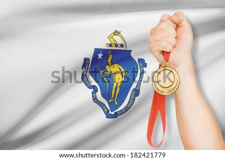Sportsman holding gold medal with Commonwealth of Massachusetts flag on background. Part of a series. - stock photo