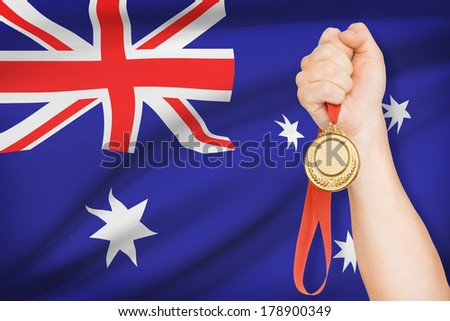 Sportsman holding gold medal with flag on background - Australia - stock photo