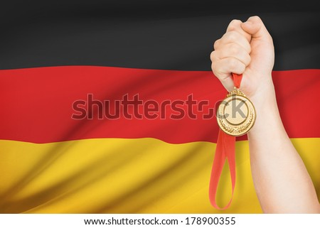 Sportsman holding gold medal with flag on background - Germany - stock photo