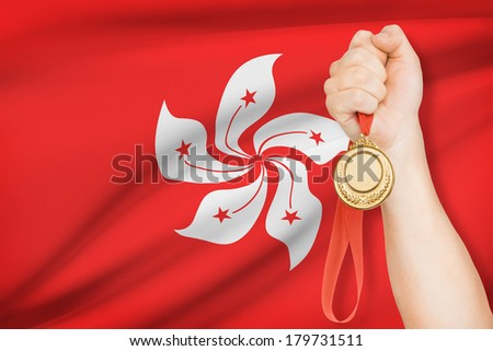 Sportsman holding gold medal with flag on background - Hong Kong Special Administrative Region of the People's Republic of China - stock photo