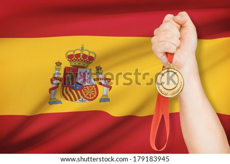 Sportsman holding gold medal with flag on background - Kingdom of Spain - stock photo
