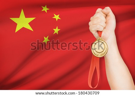 Sportsman holding gold medal with flag on background - People's Republic of China - stock photo