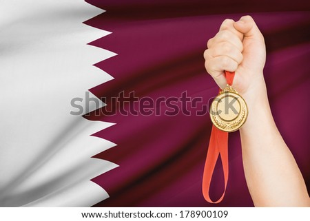Sportsman holding gold medal with flag on background - Qatar - stock photo