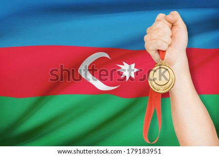 Sportsman holding gold medal with flag on background - Republic of Azerbaijan - stock photo
