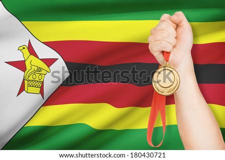 Sportsman holding gold medal with flag on background - Republic of Zimbabwe - stock photo