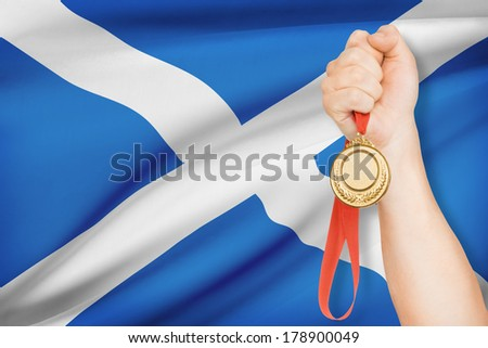 Sportsman holding gold medal with flag on background - Scotland - stock photo