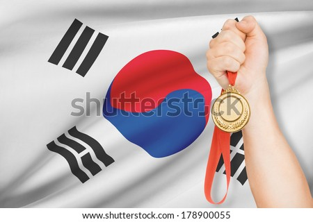 Sportsman holding gold medal with flag on background - South Korea - stock photo