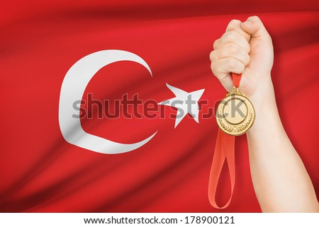 Sportsman holding gold medal with flag on background - Turkey - stock photo