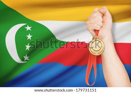 Sportsman holding gold medal with flag on background - Union of the Comoros - stock photo
