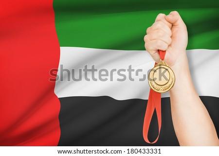 Sportsman holding gold medal with flag on background - United Arab Emirates - stock photo