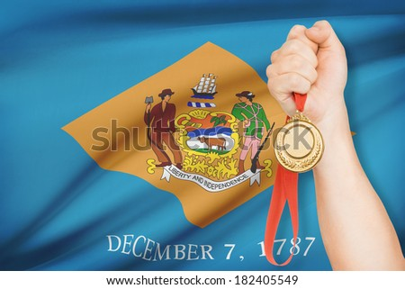 Sportsman holding gold medal with State of Delaware flag on background. Part of a series. - stock photo
