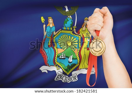 Sportsman holding gold medal with State of New York flag on background. Part of a series. - stock photo