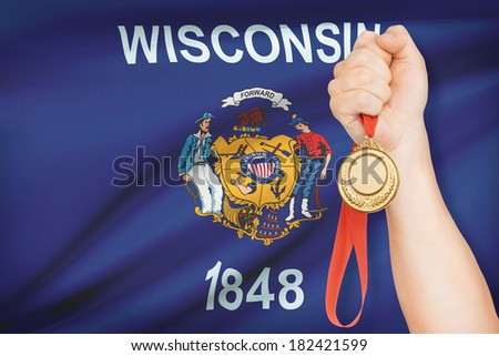 Sportsman holding gold medal with State of Wisconsin flag on background. Part of a series. - stock photo