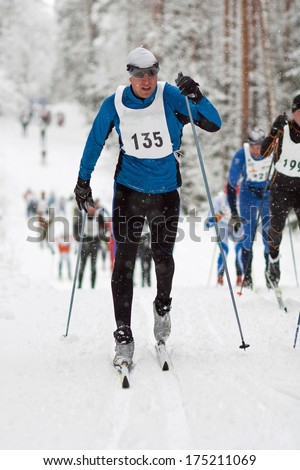 Sportsman in classic style cross country skiing race, competitors following - stock photo