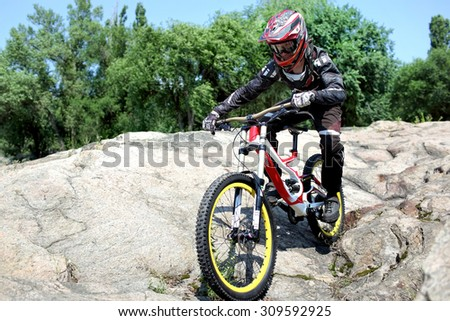 Sportsman in sportswear on a mountain bike rides on the stones in extreme style downhill - stock photo