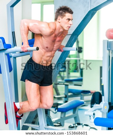 sportsman is engaged in the uneven bars at the gym