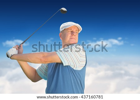Sportsman is playing golf against bright blue sky over clouds - stock photo