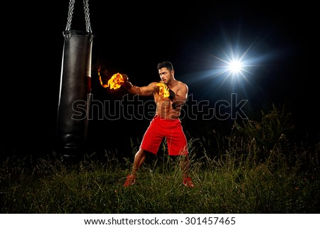 sportsman is training on the black night background, muscular body, boxing gloves in the fire, the night training training in open space on grass, boxing kick from the right hand, black punching bag  - stock photo